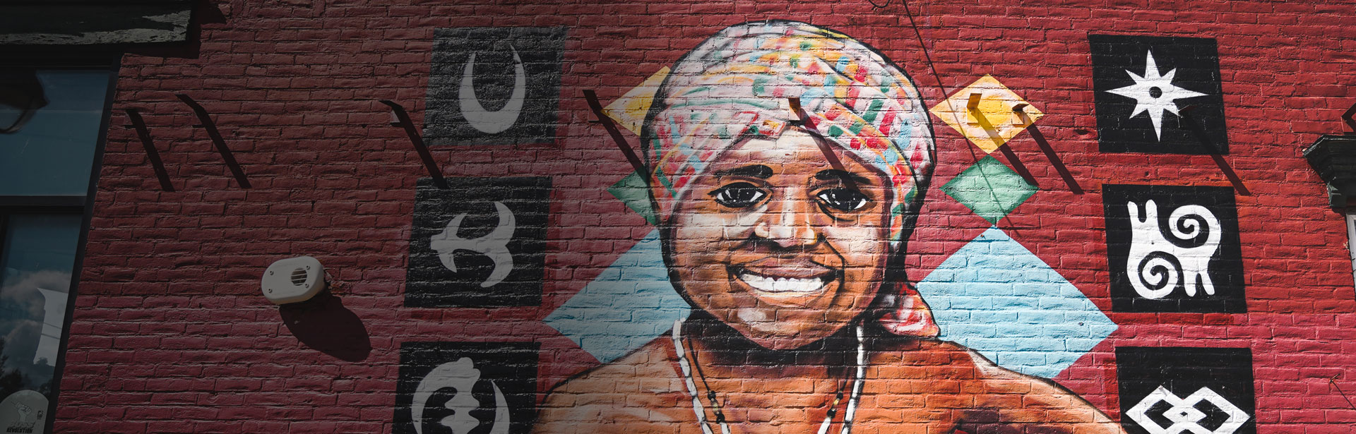 Aerial image and video courtesy of William Daugherty - Paint on brick wall on side of building of a bipoc woman smiling