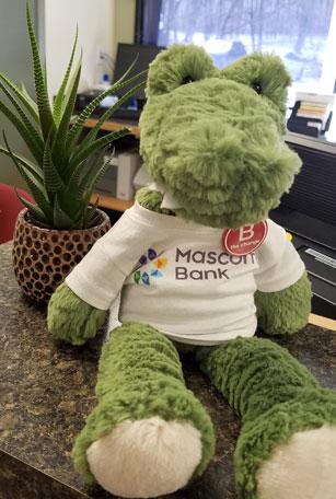 plush aligator wearing a mascoma bank tee shirt and a b the change pin
